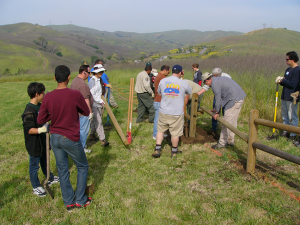 Volunteers help park staff build fencing around a group campground.