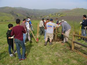 Volunteers help park staff build fencing around a group campground.